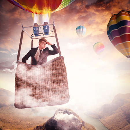 hot air balloon: Businessman looking in a hot air balloon Stock Photo