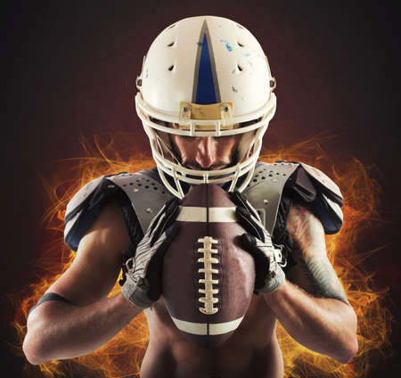 fierce competition: Football player holding ball in his hands