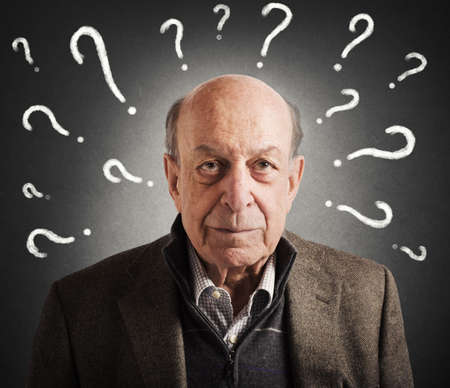 incertitude: Old man confused with many question marks Stock Photo
