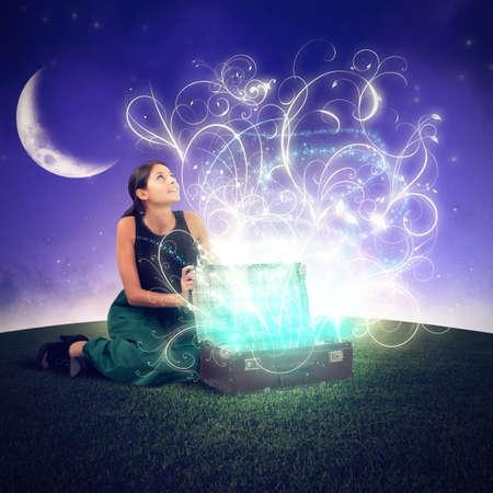 mujer con maleta: Muchacha soñadora abre una maleta que brilla intensamente la magia