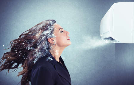 Ventilation: Frozen girl under a powerful air conditioner Stock Photo