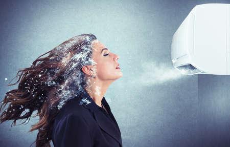 resfriado: Muchacha congelada bajo un potente aparato de aire acondicionado