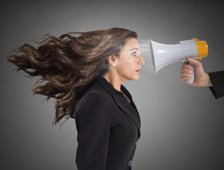 reprimand: Businesswoman frightened by the megaphone loud noise Stock Photo