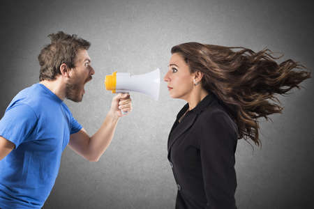 pelea: Hombre que grita con el megáfono a una mujer de negocios