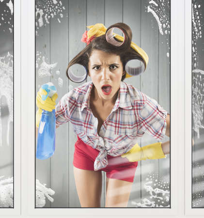 Astonished housewife with gloves and detergent spray