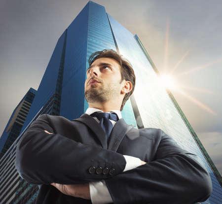 Erfolg: Erfolgreicher Geschäftsmann mit Wolkenkratzer im Hintergrund