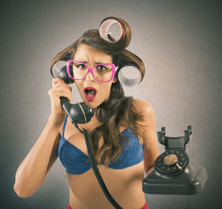 is disgusted: Girl disgusted and astonished on the phone Stock Photo