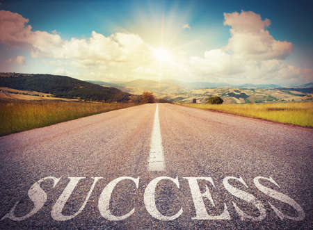 achieve goal: Road that says success in the asphalt Stock Photo