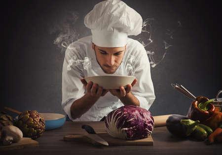 chef cocinando: Chef oler el aroma de un plato Foto de archivo