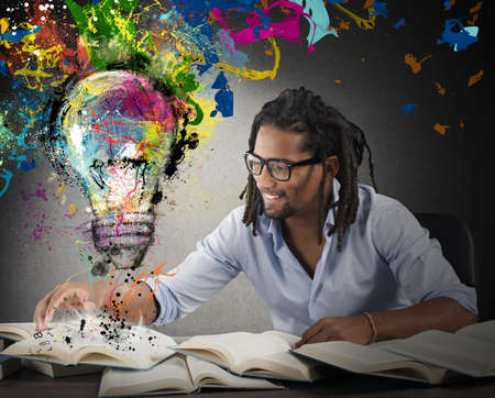 illuminate: Man reads books with above colored bulb Stock Photo
