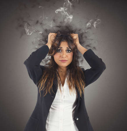 Businesswoman stressed with her head in smoke Stock Photo