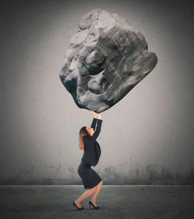 exhausted: Businesswoman holding up a big rock heavy Stock Photo