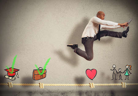 distance: Successful businessman jumps on a life rope Stock Photo