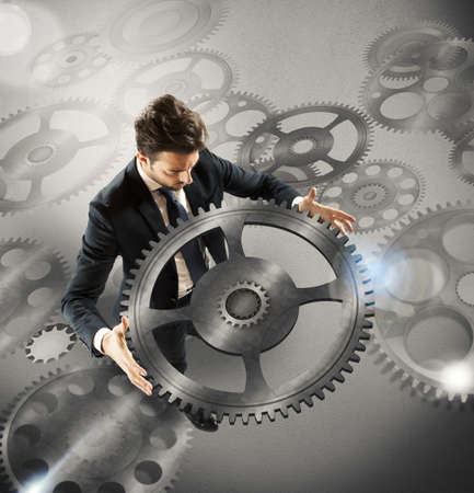 gearwheel: Businessman holds a big piece of gear Stock Photo