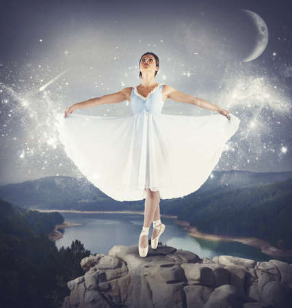 graceful: Ballerina dancing on tiptoe above a rock Stock Photo