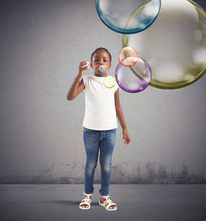 huge: Little girl plays making soap colourful bubbles Stock Photo
