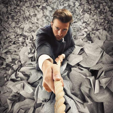 税金からロープ エスケープにしがみついて実業家 写真素材