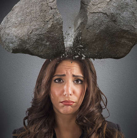 crack: Businesswoman with split boulder above her head Stock Photo