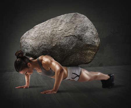 muscle training: Muskulöse Frau hebt einen Stein mit Rücken