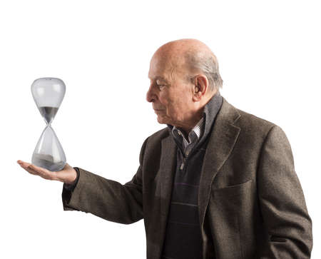 hour hand: Elderly man holds an hourglass in hand