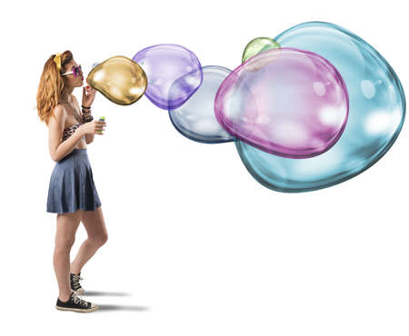 Girl has fun making colorful soap bubbles 写真素材
