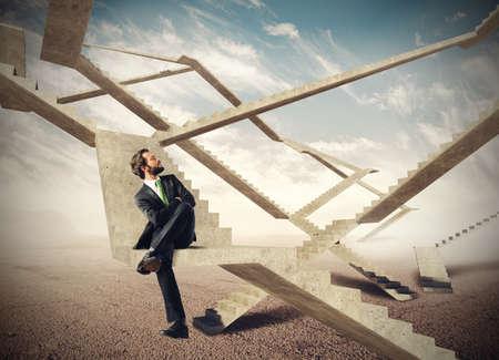 escalera: Hombre de negocios sentado y viendo las escaleras sin fin Foto de archivo