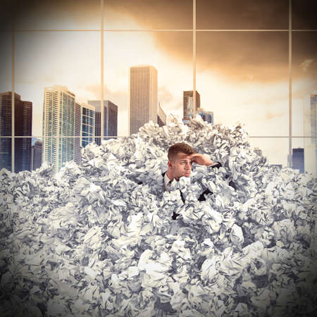 Frustrated businessman buried by balls of paper
