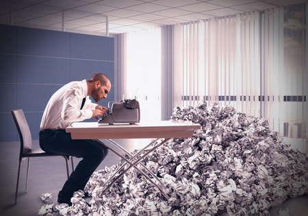 escribiendo: Hombre de negocios agotado con exceso de trabajo escribe con una máquina de escribir Foto de archivo