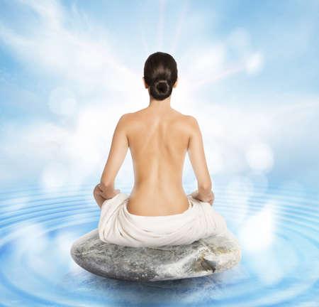 donna nuda: Donna che fa yoga seduto su una pietra
