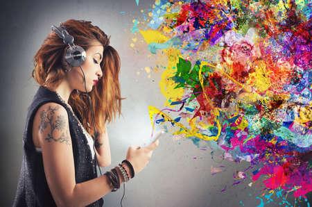 adolescente: Muchacha del tatuaje escucha música con auriculares