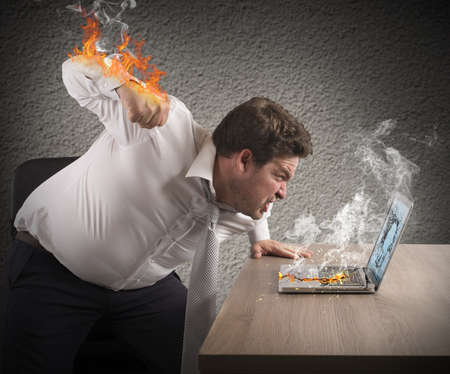 Angry man gives fiery fist to computer Stock Photo