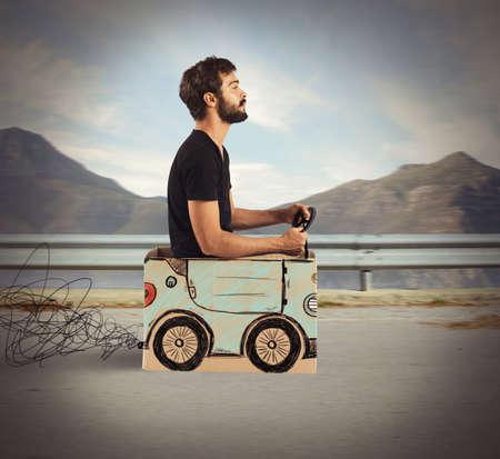 carton: Muchacho que conduce el coche de cartón en la carretera de montaña Foto de archivo