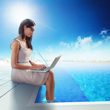 working on computer: Businesswoman working with computer in the pool Stock Photo