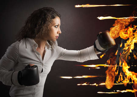 Determined woman with boxing gloves fights fire Foto de archivo
