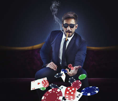 Rich gambler throws cards dice and chips Stock Photo