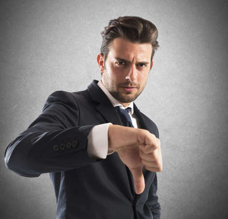 dejected: Negative mood businessman with a thumb down