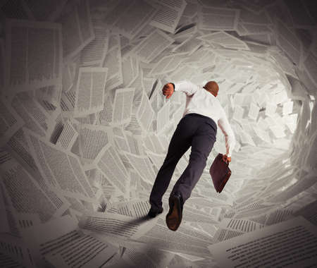 frustrate: Businessman runs through a tunnel of paper