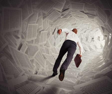 Businessman runs through a tunnel of paper