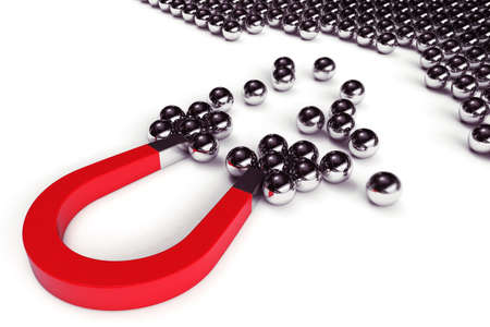 attracts: Magnet attracts steel balls from a pile Stock Photo
