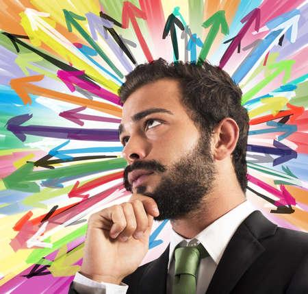 mente humana: Hombre de negocios piensa con el fondo de flechas de colores Foto de archivo