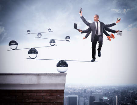 Businessman balancing on boards with iron balls Standard-Bild