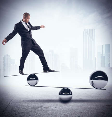 Businessman balancing on boards with iron balls Stock Photo