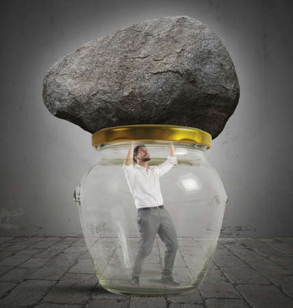 suffocating: Man trapped in a jar with rock Stock Photo