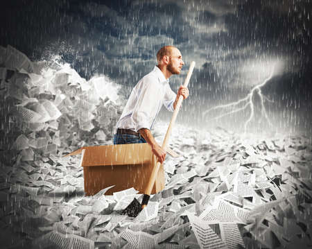 exhausted: Concept of bureaucracy with man paddling in a sea of sheets Stock Photo