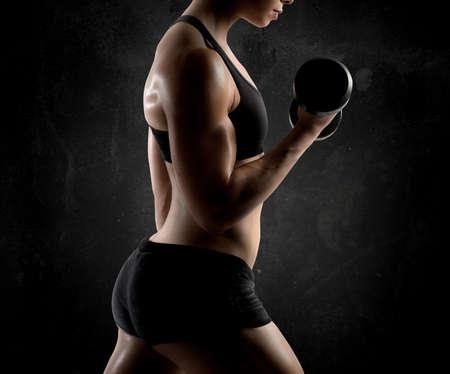 atletismo: Atlético bíceps entrenamiento muscular de la mujer con pesas