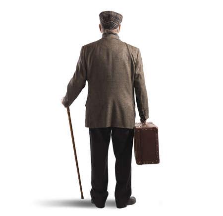 Oude man terug met een koffer en stok