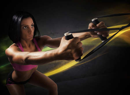 flexion: Athlete girl does fitness with trx exercise Stock Photo