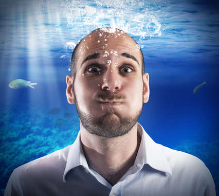 sea water: Helpless man holds his breath under water