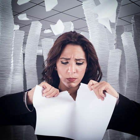 pile of papers: Woman nervous and stressed tears a worksheet