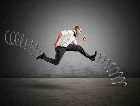 stressful: Businessman running fast with the big springs